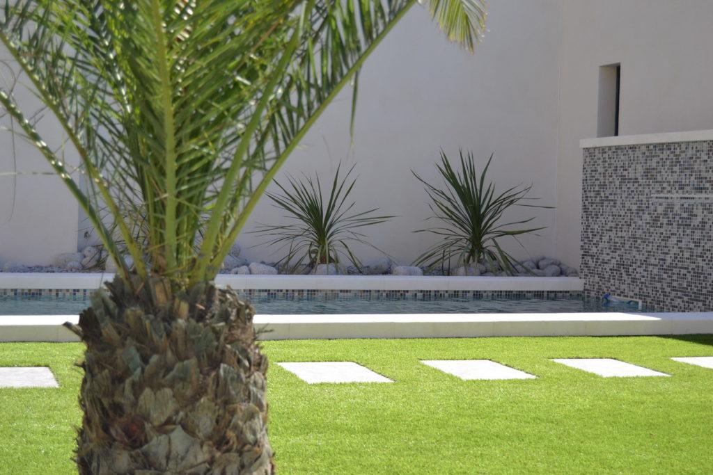 jardin pelouse et galets design avec piscine design béton projeté et mur carreaux mosaïques