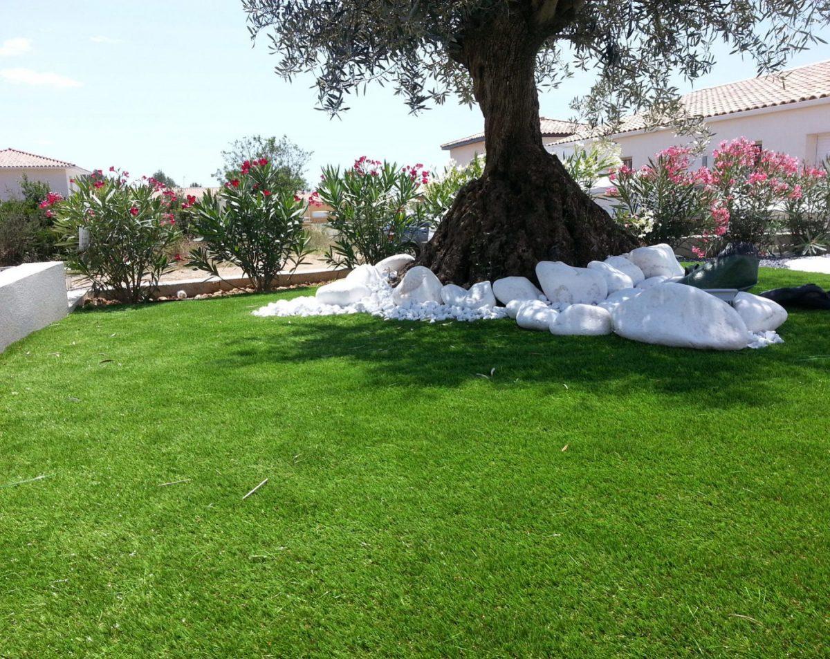 gazon vert plates fleuris et grand arbres et gros galets décoratifs