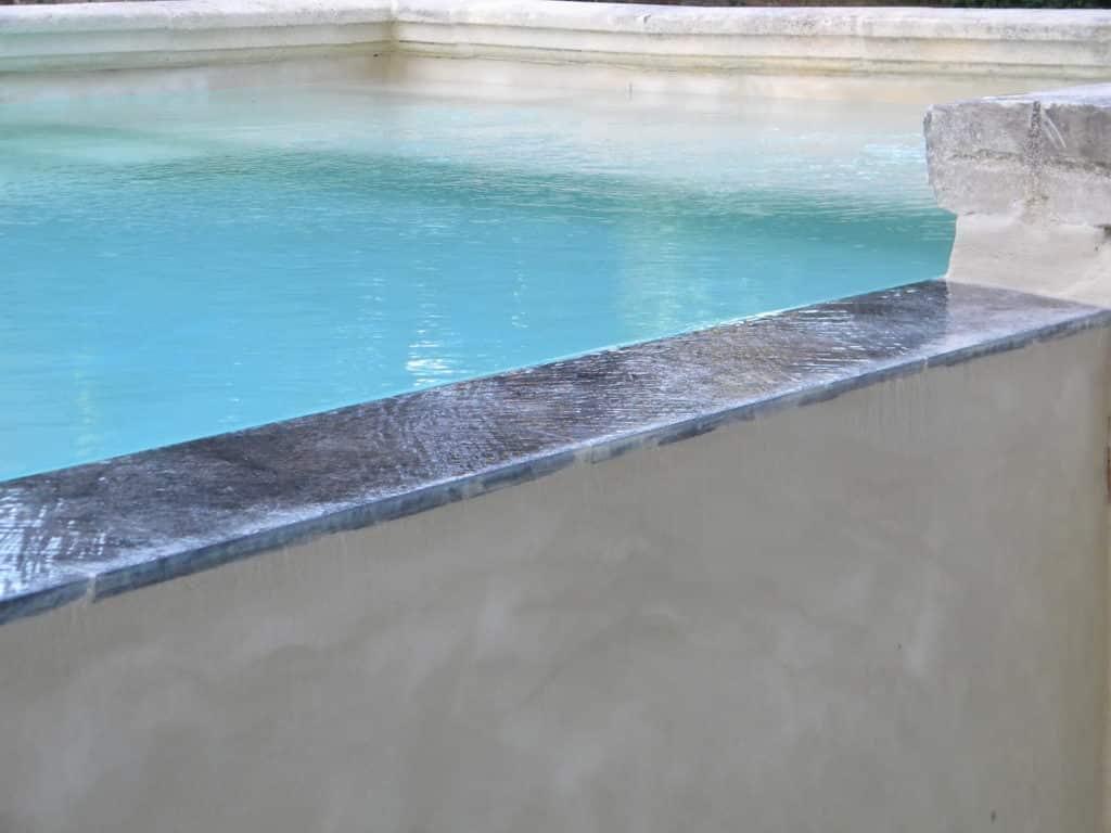 piscine débordement margelle pierre grise naturelle béton projeté