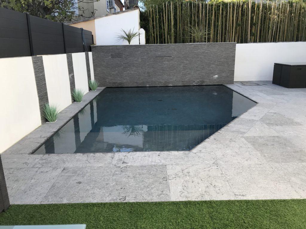 piscine revêtement gris béton projeté mur pierre grise lame d'eau